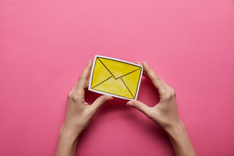 top view of yellow email sign on pink background